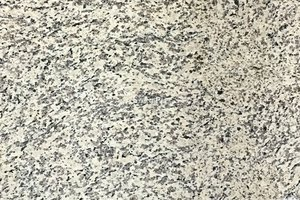 A pale granite with black and brown spotting.