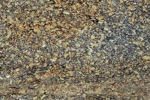 A coarse grained, gold and brown granite with black spots.