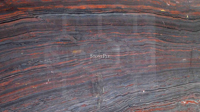 A deep red and dark grey granite with a veined texture.
