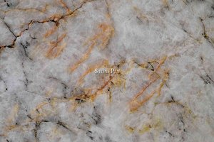 A yellow and cream granite with darker veins.