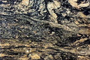 A gold and black granite with a veined texture.