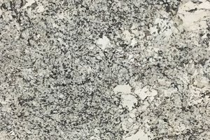 a white granite with beige variation and dense veining of brown and black.
