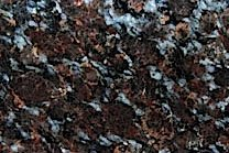 A granite with a black background with random red and brown flakes.