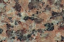 A consistant dark red granite that has brown and black flecks.