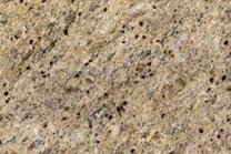 A coarse grained, beige granite with gold and grey veins.