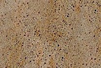 A yellow and brown granite with black dots.